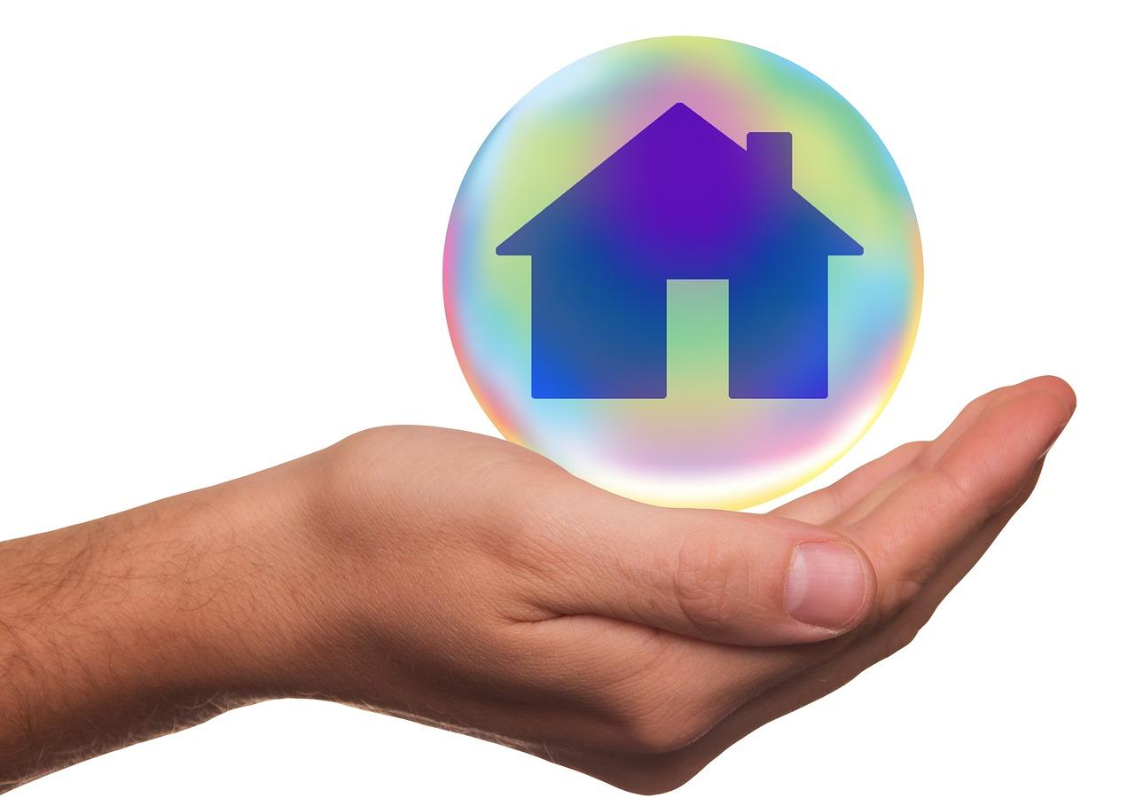 Main tenant une icône de maison protégée dans une bulle